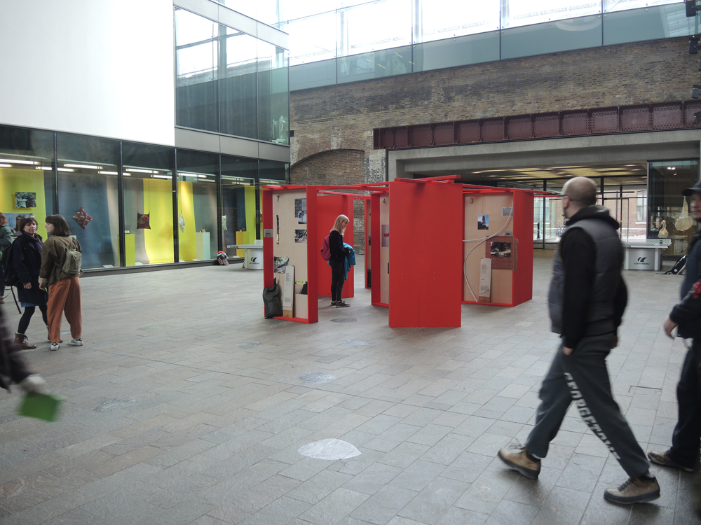 Installation at the crossing: 9 red boxes as an accessible archive, unfolding the adaption of the Assemblage Boards, its titles and texts